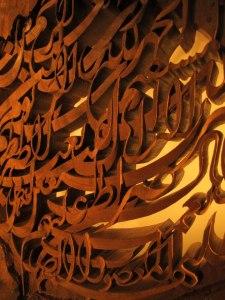 أعمال حروفية على الخشب من عمل كاميار حكمي. وعمل هذا الفنان يحرر الحروفية من سطح الرسم الى الفضاء المجسم في 3D حقيقي.